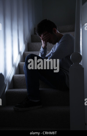 Young man sitting on the stairs, his hand covering his face. - Stock Photo