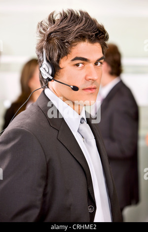 young man with headset in an office - Stock Photo