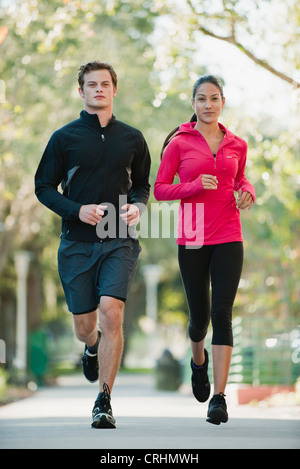 Young couple jogging side by side - Stock Photo