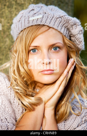 young cute blonde, longhaired woman wearing a knitted cap - Stock Photo