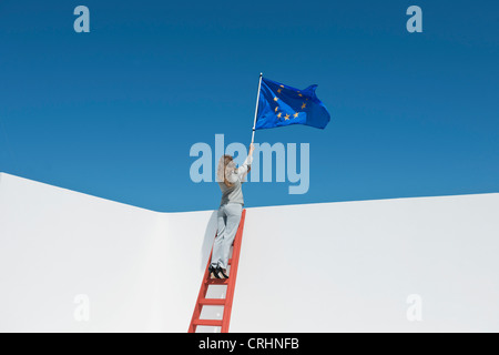 Businesswoman standing at top of ladder, holding European Union flag - Stock Photo