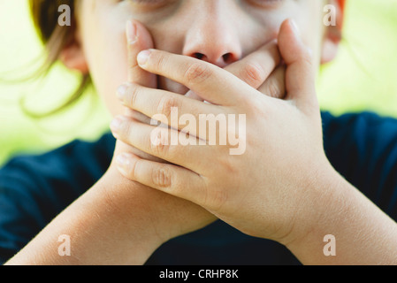 Boy covering mouth with hands, cropped - Stock Photo