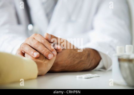 Doctor comforting patient during consultation - Stock Photo