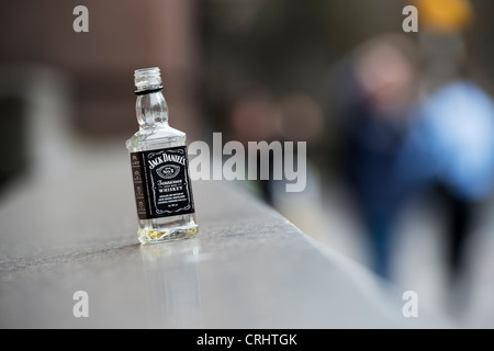 Empty miniature Jack Daniels whiskey bottle on a ledge. London. England - Stock Photo