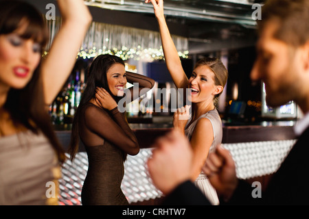 Smiling friends dancing in bar - Stock Photo