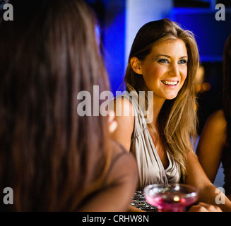 Women having drinks together at bar - Stock Photo