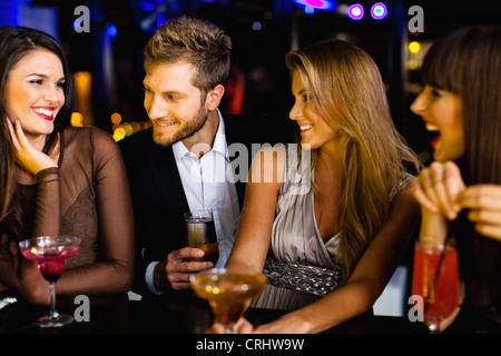 Man talking to women at bar - Stock Photo