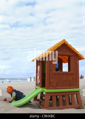 little boy during cold weather playing in the sand beside a toy house with slide, Netherlands, North Sea, Noordwijk - Stock Photo