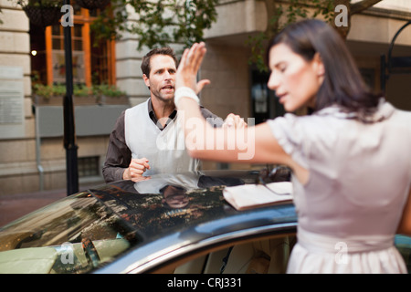 Couple arguing over sports car - Stock Photo