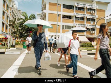Pedestrians with umbrellas cross a street in Singapore - Stock Photo