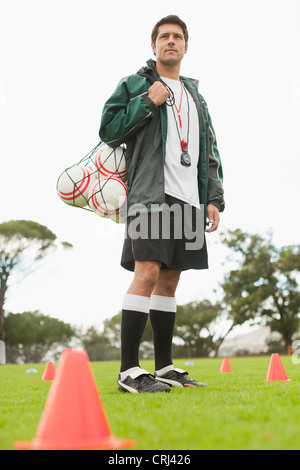 Coach carrying soccer balls on pitch - Stock Photo