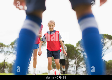 Girl playing soccer on pitch - Stock Photo