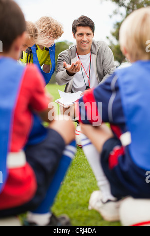 Coach talking to childrens soccer team - Stock Photo