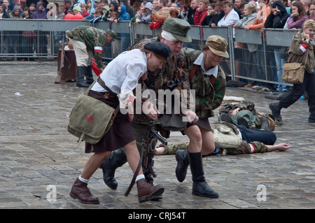 Home Army soldier, nurse, carrying the wounded, 1944 Warsaw Uprising re-enactment at Rynek in Wrocław, Lower Silesia, - Stock Photo