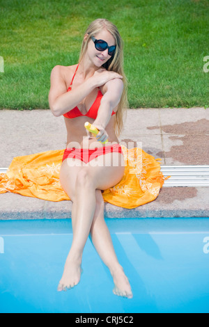 young woman wearing a bikini and sunglasses sitting at a pool putting sun lotion on her body - Stock Photo