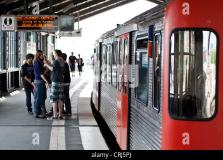 Group of young people waiting for tram at station Baumwall in Hamburg, Germany. - Stock Photo