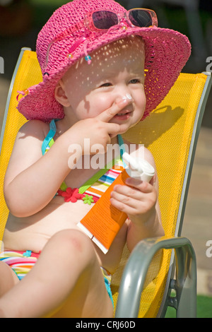 little girl in a bikini with a sun hat sitting in a children's chair putting sun milk on her nose - Stock Photo