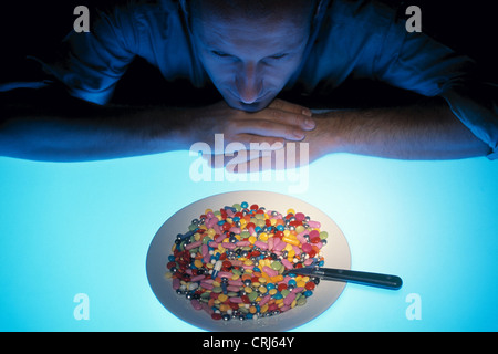 Man looks with head propped on a plate with meal tablets - Stock Photo
