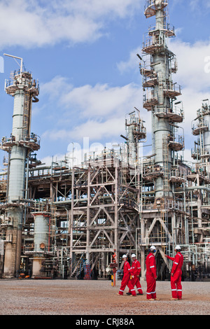 Workers talking at oil refinery - Stock Photo