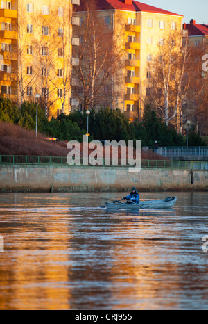 Caucasian male trolling from a rowboat at river Oulujoki at the center of the city of Oulu , Finland - Stock Photo