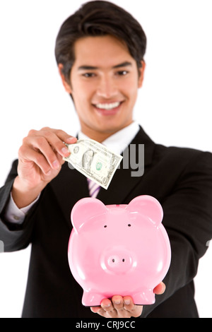 young businessman putting a bill into his piggy bank with a smile - Stock Photo