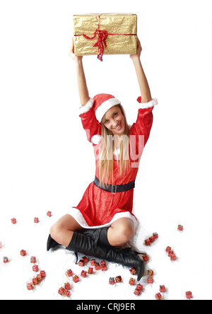 young blonde woman in Santa Claus dress holding gift into the air with a smile - Stock Photo