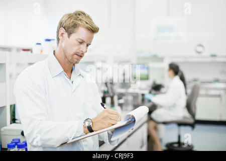 Scientist writing on clipboard in lab - Stock Photo
