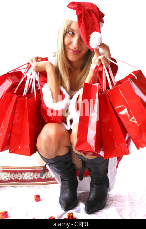 young blonde woman in Santa Claus dress with lots of shopping bags and presents - Stock Photo