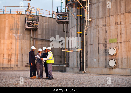 Workers reading blueprints at plant - Stock Photo