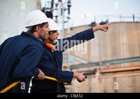 Workers talking at chemical plant - Stock Photo