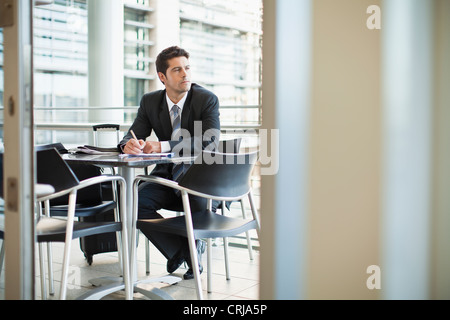 Businessman making notes in cafe - Stock Photo