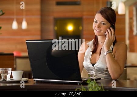 young woman sitting in a cafeteria at a laptop phoning with a mobile - Stock Photo