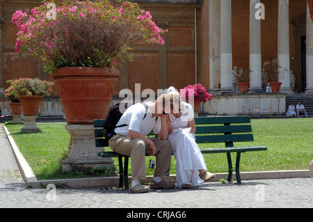 Young couple dozing with their heads together, Vatican City Gardens - Stock Photo