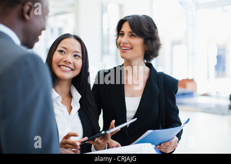 Business people talking in lobby - Stock Photo