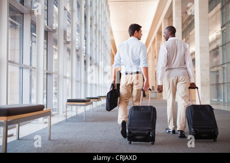 Businessmen rolling luggage in hallway - Stock Photo