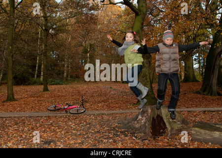 A girl and a boy jumping happily off a tree-trunk in a park in autumn - Stock Photo