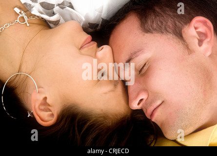 beautiful couple in love sleeping with heads together on the floor - Stock Photo