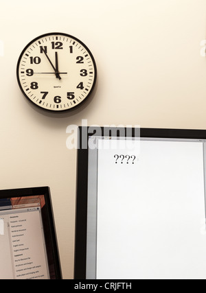 Concept for urgent decision making with clock on paper and question mark on pad - Stock Photo