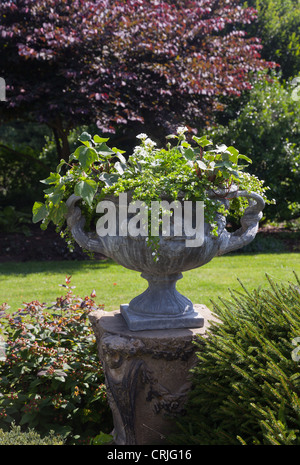 Ornate shaped stone urn on pillar with leaves in english style garden - Stock Photo