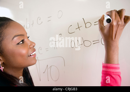 female math student writing equations on the wall panel - Stock Photo