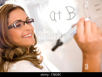 female math teacher with glasses writing a simple equation on the wall panel - Stock Photo