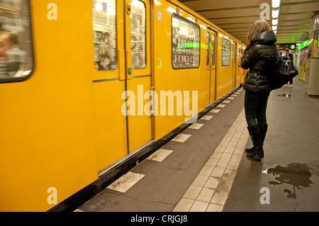 Berlin, Germany. U-Bahn (underground railway). Woman waiting on the platform, train arriving, puddles - Stock Photo