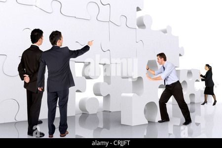 young business team building a wall of giant puzzle pieces - Stock Photo