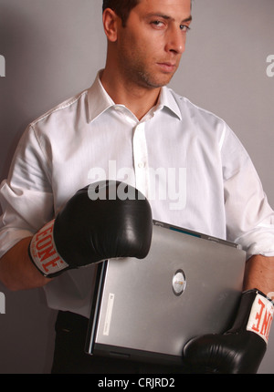 young businessman holding a laptop wearing boxing gloves - Stock Photo