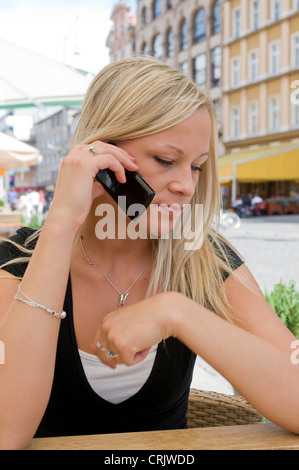 young fair-haired woman in a caf� with a cell phone talking - Stock Photo