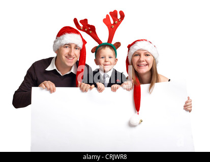 smiling young family wearing Santa caps of an elk antler holding an empty white panel - Stock Photo