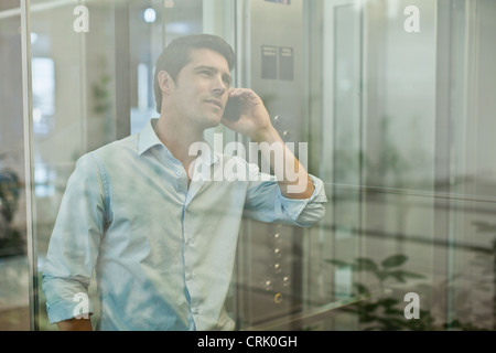 Businessman on cell phone in elevator - Stock Photo
