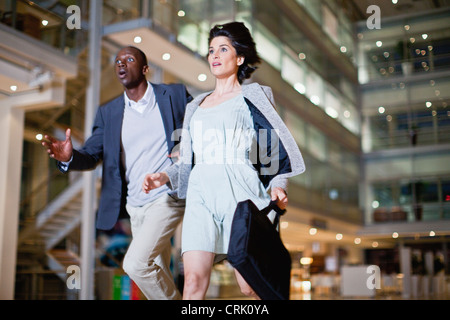 Business people running in lobby - Stock Photo