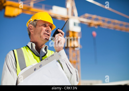 Worker using walkie talkie on site - Stock Photo