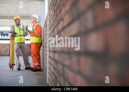 Workers talking at construction site - Stock Photo